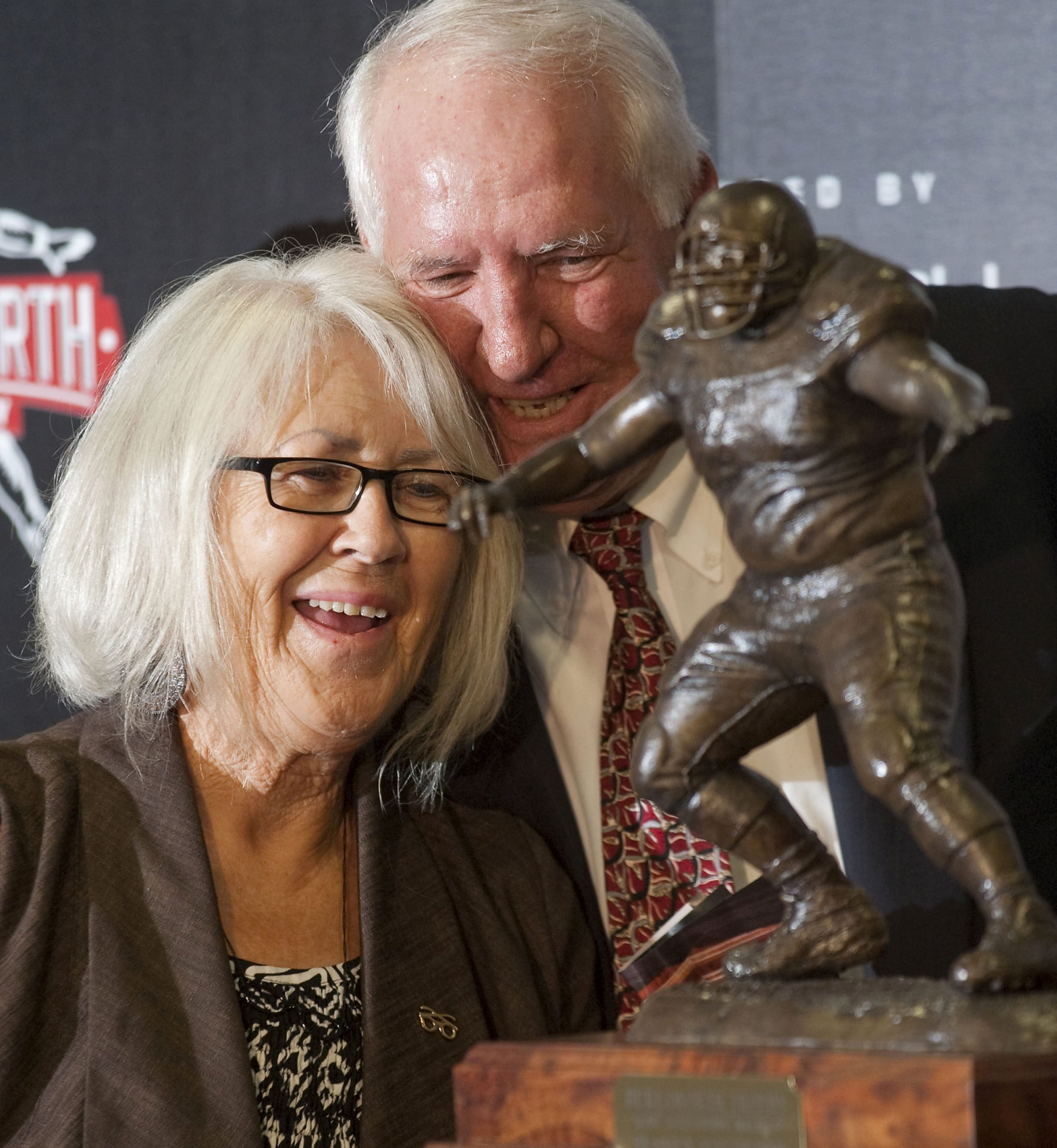 Former Arkansas head Coach Danny Ford hugs Barbara Burlsworth in August 2010 in Fayetteville after the unveiling of the Burslworth Trophy in honor of her son, Brandon. The trophy is given annually to a college player who started his career as a walk-on. (AP photo by Beth Hall)