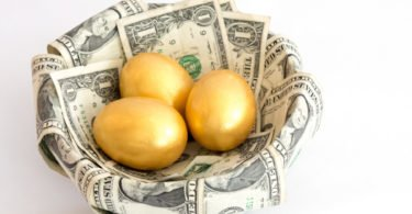 Image of three golden eggs sitting in a nest made of dollar bills.  The nest is set against a white background.   The eggs represent three separate investments, or nest eggs, of equal size.