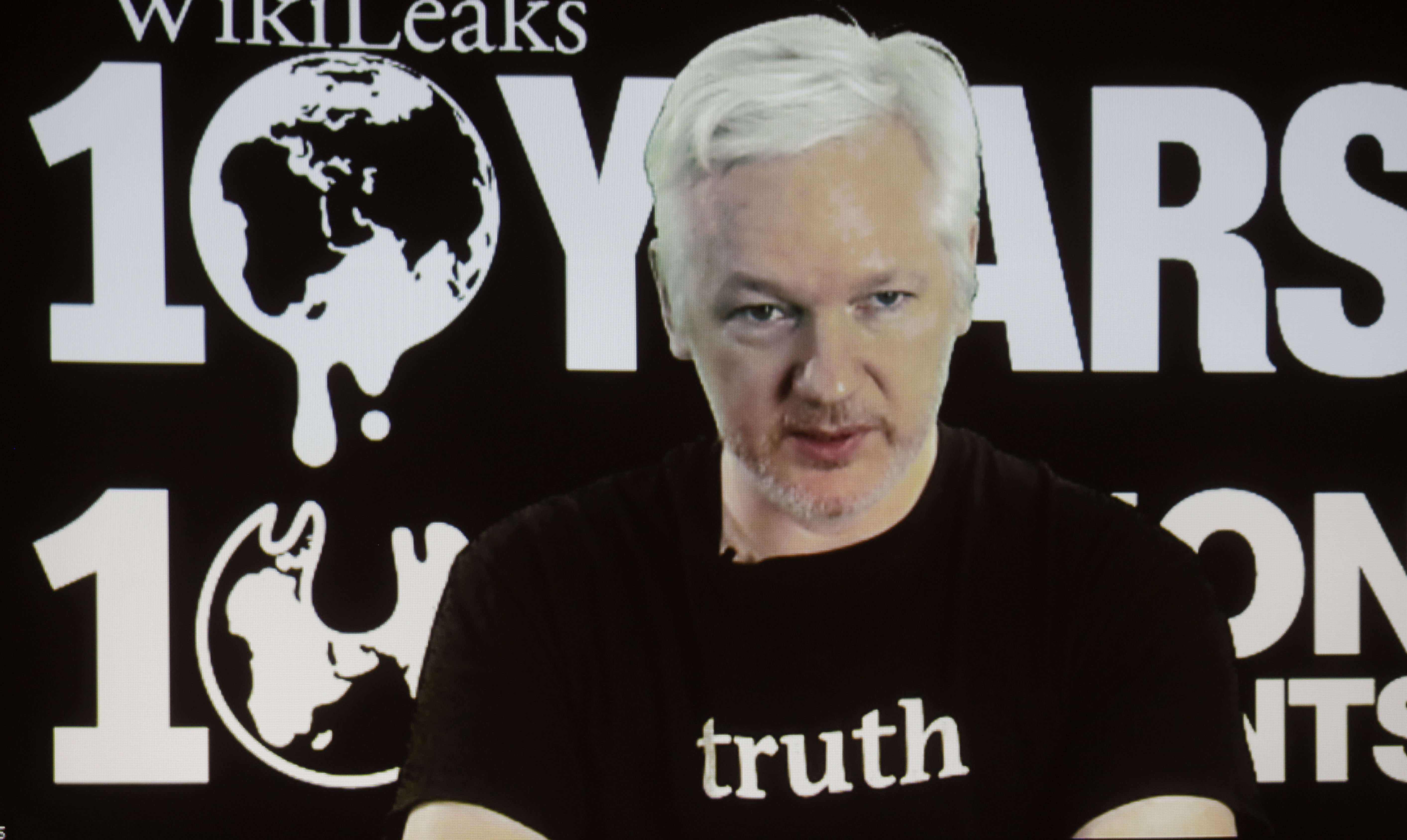 FILE - In this Oct. 4, 2016 file photo, WikiLeaks founder Julian Assange participates via video link at a news conference marking the 10th anniversary of the secrecy-spilling group in Berlin. Assange may be stuck in the Ecuadorean Embassy and cut off from the internet, but he's closer than ever to testing a hypothesis he first outlined nearly a decade ago. Can total transparency defeat an entrenched group of insiders? (AP Photo/Markus Schreiber, File)