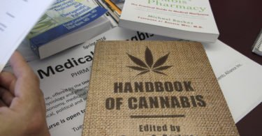 In this Dec. 4, 2015 photo, books about marijuana lay on a table in the office of University of Vermont pharmacology professor Wolfgang Dostmann in Burlington, Vt. The College of Medicine is offering a new class on the science of medical marijuana. UVM is one of the first accredited academic programs in the country to offer a pharmacology class on medical cannabis. Professors said they are hampered by a lack of research on the topic. (AP Photo/Lisa Rathke)
