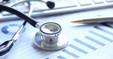 A doctor's stethoscope with financial statement
