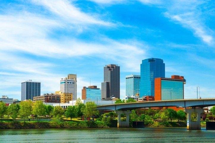 Little Rock downtown skyline with the Arkansas river in the foreground and soft wispy clouds in the background.