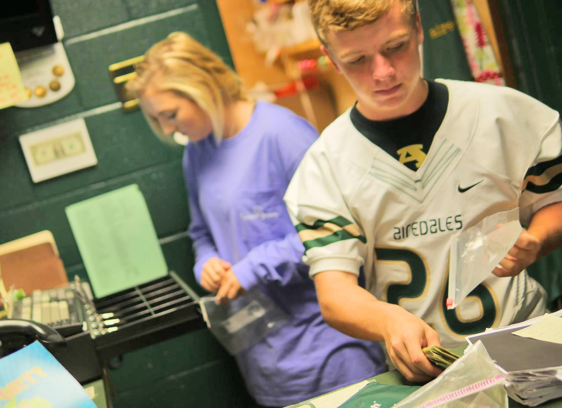 Alma High School seniors Kaitlyn Jackson and Dean Whitmire count their earnings at the end of the day.
