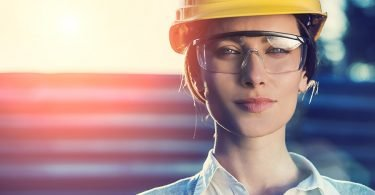 beautiful woman civil engineer or architect with yellow protective industrial helmet and protective glasses close up